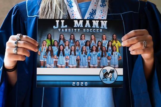 J.L. Mann senior Erika Manfre holds up a photo of the 2020 soccer team taken by Ohana Sports Photography in her home Friday, April 24, 2020.