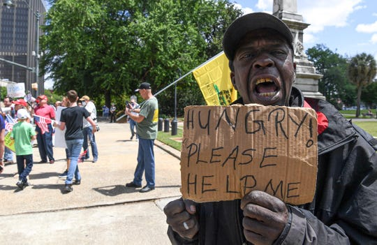 """Stacy Tazz, out of work for five weeks from a restaurant in Columbia, chants """"Open our county, open our state"""" with fellow demonstrators during the Drive To Thrive SC protest at the State House in downtown Columbia Friday, April 24, 2020."""