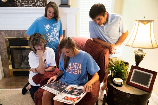 J.L. Mann senior Erika Manfre and her family look through photos of her time on the soccer team Friday, April 24, 2020. Counter clockwise from left are her mother, Shellie and siblings Rachele and Teddy.