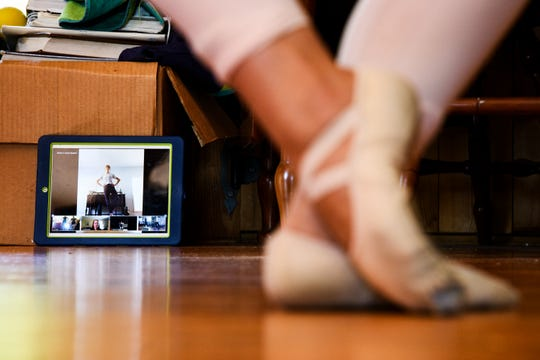 Madalin Beam, 18, goes through warmup exercises as she and her sister Haven, 15, participate in an online ballet lesson in their home Tuesday, April 21, 2020.