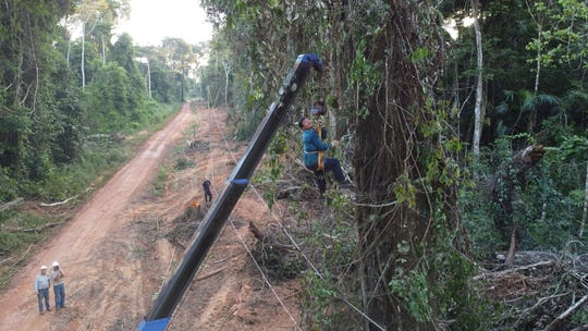 A local man works to clear vines from the power line with a machete, while hanging from a crane.