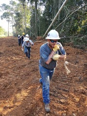 Linemen Led By Josh Fatouros Of Park Electric Cooperative hand pull a line