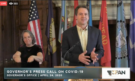 Gov. Steve Bullock talks Friday about COVID-19 efforts in Montana. With him is sign language interpreter Victoria Gregori.