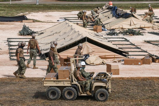 Military personnel assemble multiple rows of tents within the confines of the Navy's South Finegayan Royal Palms housing area in Dededo on Friday, April 24, 2020.