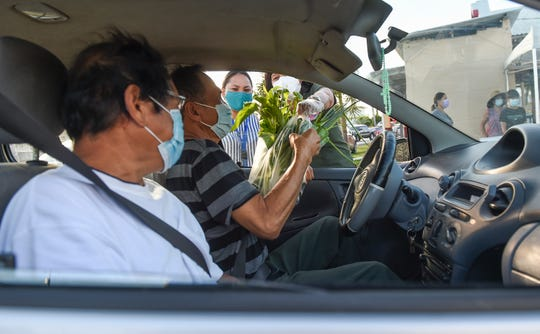 Barrigada Mayor June U. Blas, with volunteer Sheleena Cruz, gives free produce to residents at Guahan Sustainable Culture's drive-thru service near the Guam Public Library System Archival Center in Barrigada, April 24, 2020.