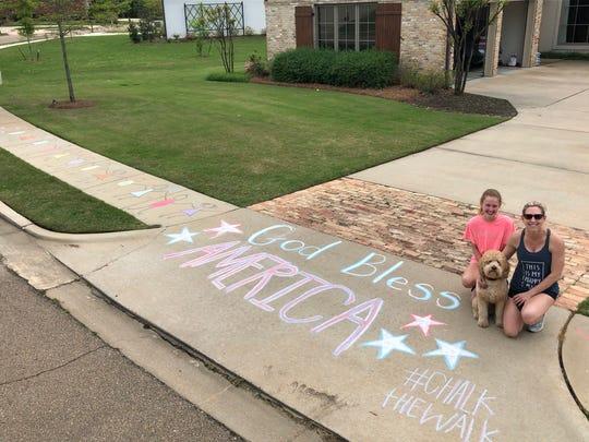 Hollis and Max Wondries with their dog, Rover, show off their chalk design that decorates their sidewalk in the Bridgewater neighborhood. The neighborhood magazine, Bridgwater Living, encouraged residents to decorate their sidewalks with chalk.