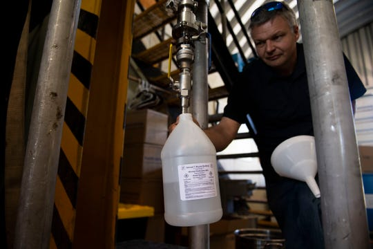 Samuel Bryant, owner of Samuel T Bryant Distillery LLC, fills up a gallon of hand sanitizer in Jackson, Tenn., on Thursday, April 16, 2020. Bryant changed his business model from making moonshine to using whiskey for hand sanitizer.