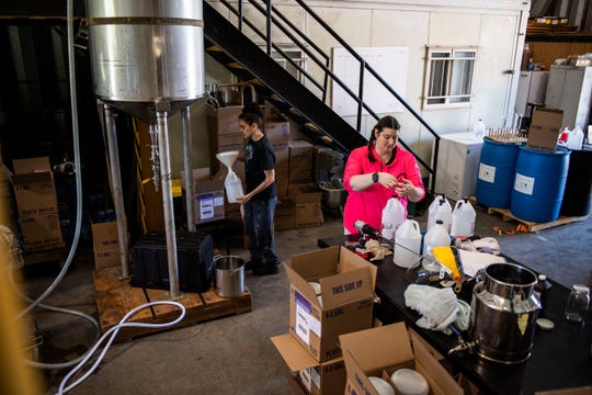 Anastasia Brown fills up a gallon of hand sanitizer as Nikki Cloar tapes down the bottles and packs them into boxes to ship out to a health facility at Samuel T. Bryant Distillery in Jackson, Tenn., on Thursday, April 16, 2020.