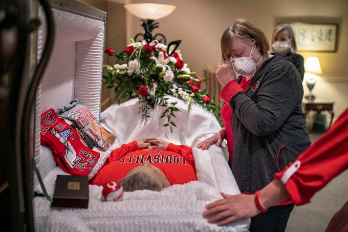 """Brenda Long, right, cries as she sees her husband, Rick Long, for the first time since before he passed in the Norton Audubon Hospital on March 30, 2020 from COVID-19. Headaches surrounded his funeral planning, with complications involving a funeral home and Brenda being diagnosed with COVID-19 herself. The family was happy to be able to honor a man that was greatly loved by many and finally lay him to rest Friday. """"We are not just a statistic or a news story,"""" Rick's daughter-in-law, Bridget Abell, said. """"We are a real, average American family that lost their loved one and we never saw it coming."""" April 24, 2020"""