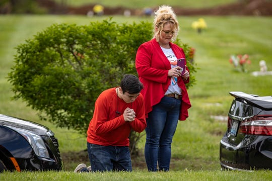 Rick Long's grandson, Donnie Abell, clasps his hands as sits on his knees beside his mother, Bridget Abell, during the funeral service for Rick Long on Friday.