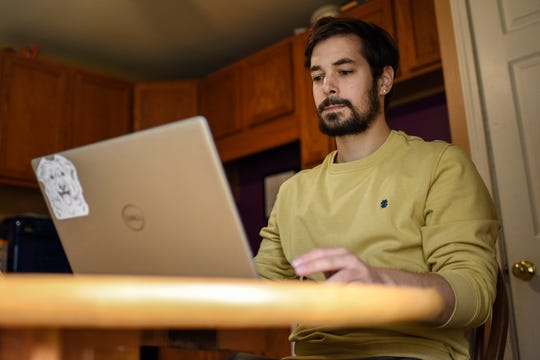 Darren Incorvaia, chief information officer for the MSU Graduate Employees Union, works on his computer in his home on Friday, April 24, 2020, in Lansing.