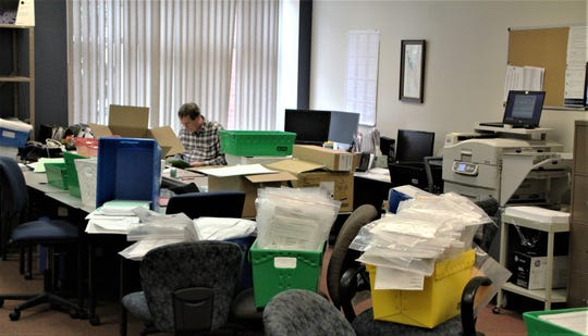 Marion County Board of Elections employee Terry Bechtle appears trapped behind a mountain of absentee ballot applications and completed ballots that the office staff has been mailing out to voters and processing once returned, respectively. Today (Monday) is the deadline for completed ballots being mailed to the office to be postmarked. Primary election day is Tuesday.