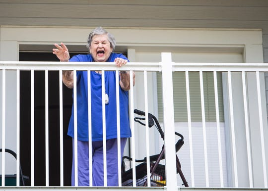 Jane Smith waves from her balcony to her family in the courtyard at Heritage at Irene Woods in the Memphis, Tenn., on Friday, April 24, 2020.