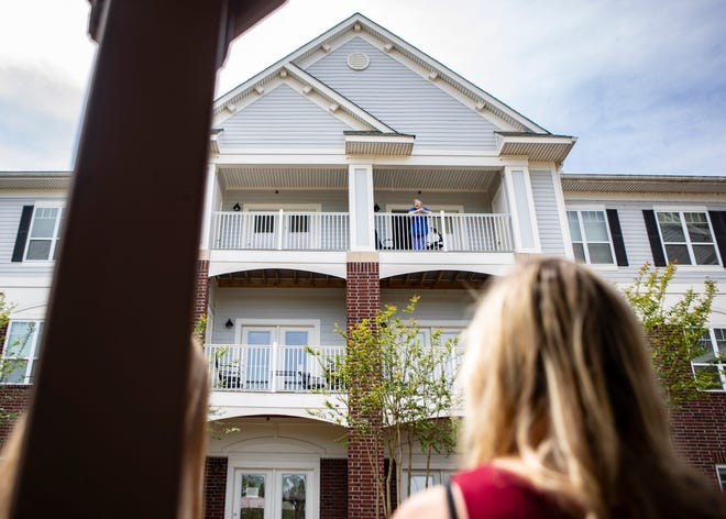 Jane Smith waves from her balcony to her family in the courtyard at Heritage at Irene Woods in the Memphis, Tenn., on Friday, April 24, 2020. The senior living facility isn't allowing visitor due to COVID-19.