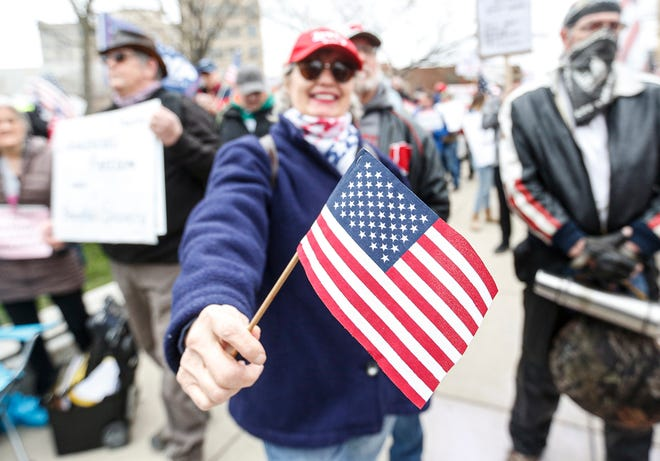 A woman holds an American flag during a protest against Gov. Tony Evers' stay-at-home order on April 24. The Shorewood Foundation had planned to plant American flags in front of every home in Shorewood, but those plans were dropped after hearing complaints from residents.
