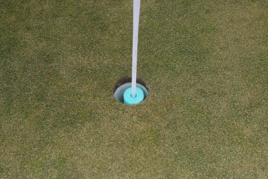 A cut-up foam swimming noodle sits in a cup at Whitnall Park Golf Course so that golfers can grab their ball out without touching the cup or the flag.