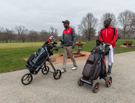 Anthony Ross Jr. and his father, Anthony Ross Sr., of Menomonee Falls head out for an afternoon of golfing at Wanaki Golf Course in Menomonee Falls on Friday, April 24, 2020. Courses across the state were allowed to open at 8 a.m. in accordance with Gov. Tony Evers' revised safer-at-home order.