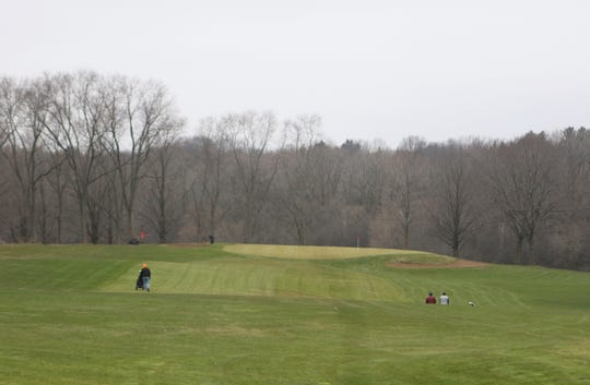 Golfers stroll down the fairway at Whitnall Park Golf Course on the first day of play of the season on April 24, 2020.