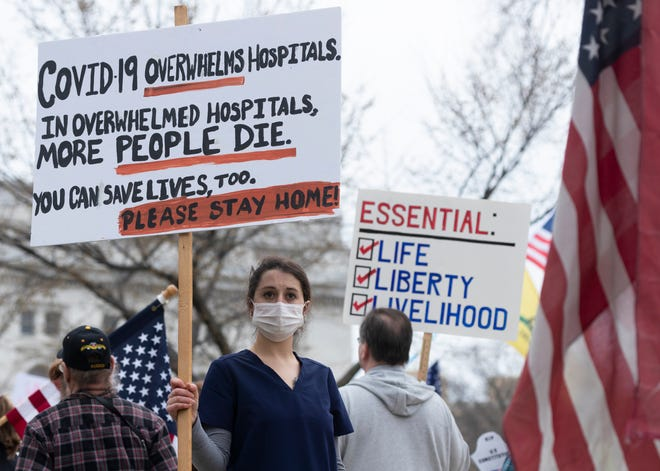 A nurse holds a sign supporting business closures amid people protesting Gov. Tony Evers' stay-at-home order Friday at the State Capitol in Madison. (Photo: Mark Hoffman/Milwaukee Journal Sentinel)