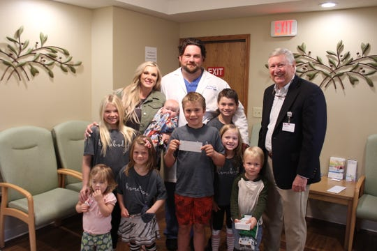 """The Bradley family presented the Baxter Regional Medical Center Foundation with a check for $17,455 Thursday afternoon. The donation represented funds raised through the sale of """"Homebody"""" t-shirts created by the family's blog, The Bradley Bunch, and the Pink Sprout Paper Company to benefit the hospital."""