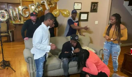 In this still image from video provided by the NFL, Noah Igbinoghene seated, reacts during the NFL football draft Thursday, April 23, 2020, in Trussville, Ala. Igbinoghene was selected by the Miami Dolphins. (NFL via AP)