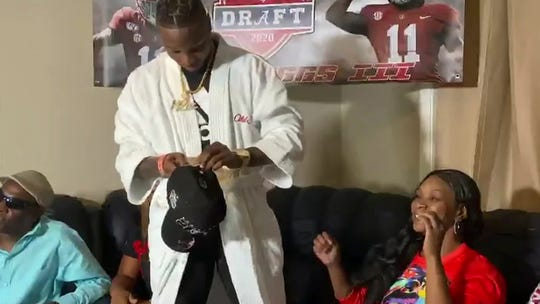 In this still image from video provided by the NFL, Henry Ruggs III gets ready to put on a Las Vegas Raiders cap after being selected by the team in the first round of the NFL football draft Thursday, April 23, 2020. (NFL via AP)