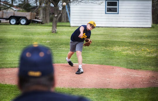 Bob Gillum coaches two of his grandsons using the family's backyard pitching mound Thursday, April 23, 2020.
