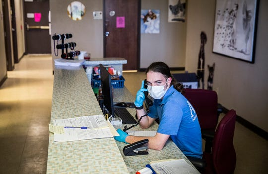 Muncie Animal Care and Services staff take calls inside their closed-to-the-public facility Friday, April 24, 2020.