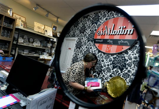 Julie Gammon Wyatt packages items together for a customer at her Initial This Shop on April 24, 2020, in Hendersonville, Tenn. Julie Gammon Wyatt works three to four hours a day meeting online orders and sets the products outside her store's front doors for customers to come to pick them up.