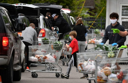 Volunteers move shopping carts of food into position to unload them at waiting cars Friday, April 24, 2020, at The Fairgrounds Nashville. One Generation Away charity asks no questions and makes no one fill out forms to get food.