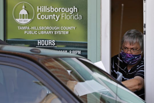 In this Friday, April 17, 2020 file photo, Hillsborough County Library service worker Stephen Duran passes out reemployment forms to a motorist at the Jimmie B. Keel Regional Library in Tampa.