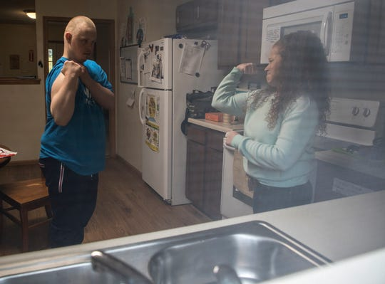 Direct Support Professional (DSP) and site supervisor, Natalie Brown, challenges Derek Singleton to show off his biceps as they prepare lunch in the group home where he lives.