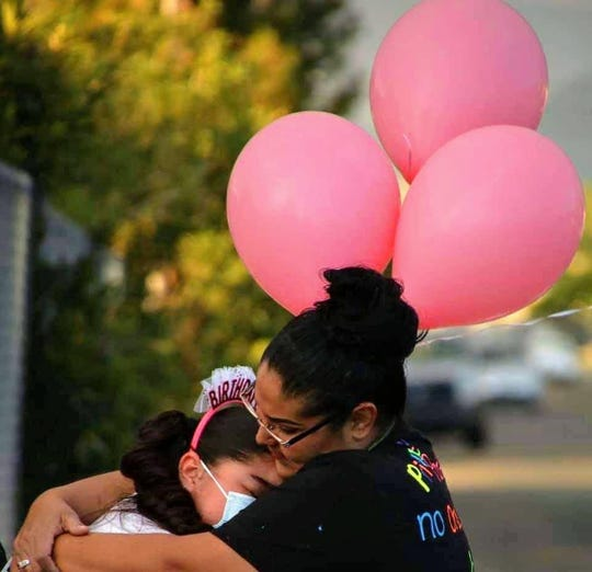 Azariah Gardea, 10, hugs her mother, Veronica Gardea Rosales, as she is moved to tears after she was surprised with a parade for her 10th birthday on Wednesday, April 22, 2020.