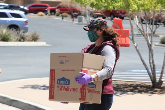 Shaunna Spears brings a box of food to a car during a food drive at Piñon Hills Community Church on Friday, April 24, 2020, in Farmington.