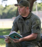 """Santa Rosa County Sheriff's Office Deputy Clay Smith reads a chapter of the children's book """"A Boy Called Bat"""" on Friday as part of the school district's new remote learning initiative aimed at creating cohesiveness for the district's students in kindergarten through fifth grades."""