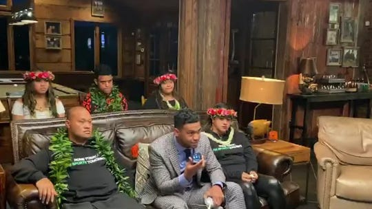 Tua Tagovailoa, front center, holds up a phone during the NFL Draft.