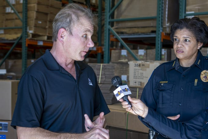 Phoenix Police Chief Jeri Williams, listens to Steve Tuttle, a Principal from Axon (which makes Tasers) donating 12,000 medical masks, 300 gallons of hand sanitizer and 5000 pair of gloves to the Incident Management Team which will supply the Maricopa County Public Safety partners.