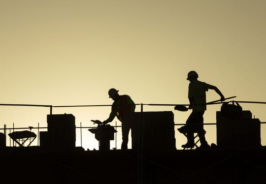 Workers build a tower at the Phoenix Battery Lofts construction site in downtown Phoenix on April 23, 2020.