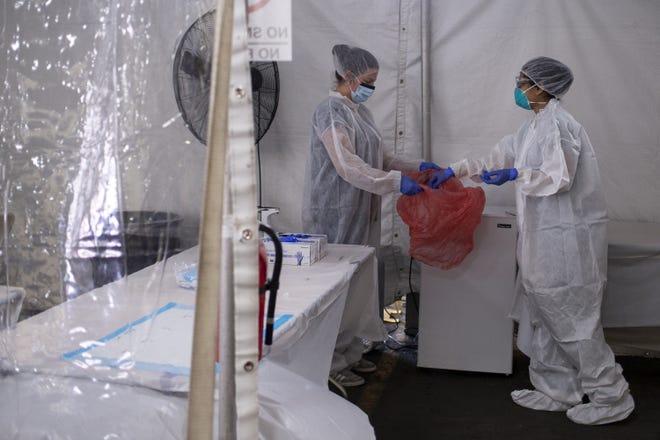 Manuela Littler and Natasha Bhuyan put away a COVID-19 test sample on April 23, 2020, at a One Medical drive-thru testing site in Scottsdale, Ariz.