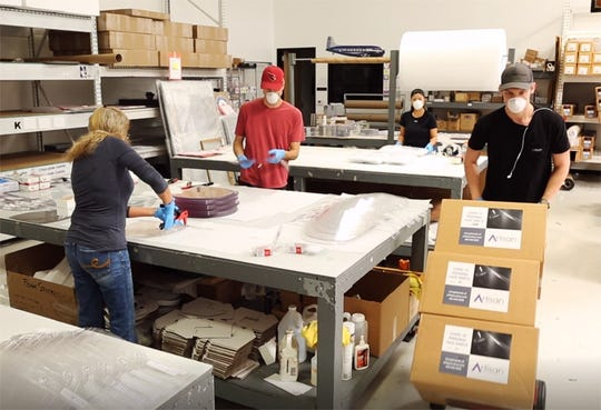 When the material arrived, the staff at Artisan Colour in Scottsdale jumped to get started, wearing gloves and face masks. They are working split shifts to maintain a safe distance from each other, with half the staff in the office at a time.