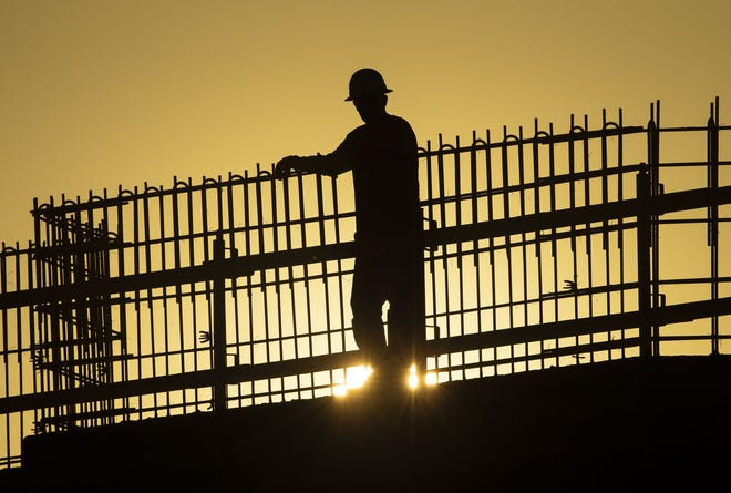 A worker leans on a rebar structure at sunrise at the PHX Sky Train Rental Car Center construction site in Phoenix on April 23, 2020.
