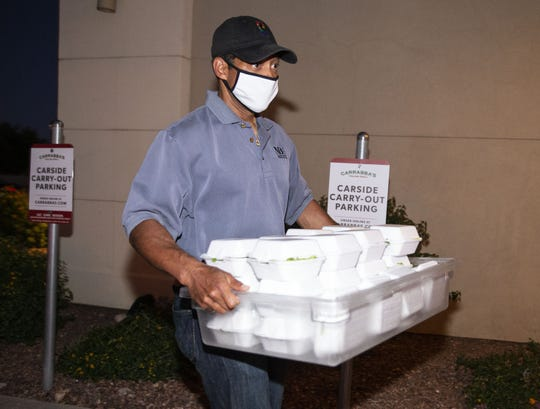 Apr. 23, 2020; Peoria, AZ, USA; NBA referee and Phoenix native Bill Kennedy loads-up meals at Carrabba's Italian Grill in Peoria, that he is donating and delivering to healthcare workers at Banner Thunderbird Hospital in Glendale. Mandatory Credit: Rob Schumacher/The Arizona Republic via USA TODAY NETWORK