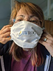 A Sacred Heart Rehabilitation Center employee wears a mask made by Blue Water Recovery and Outreach Center.