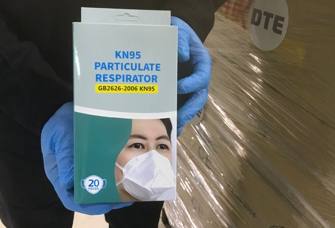 Trevor Lauer, president and chief operating officer for DTE Electric, holds a box of  N-95 respirator masks on Thursday, April 23, 2020, in St. Clair County.  The box was part of the second donation of 10,000 masks from DTE Energy.