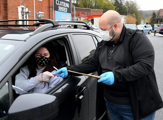 Sherri Voxakis of New Salem places an order with Glen Rock Mill Inn owner Brandon Hufnagel during Fells Point Wholesale Meats' drive-up meat sale at the inn Friday, April 24, 2020. About 100 vehicles converged on the parking lot there for seafood, meats and poultry products. The restaurant also offered soups and crab cakes for sale. Selected items were available for a donation to The Well, Immanuel United Methodist Church's local mission. Bill Kalina photo