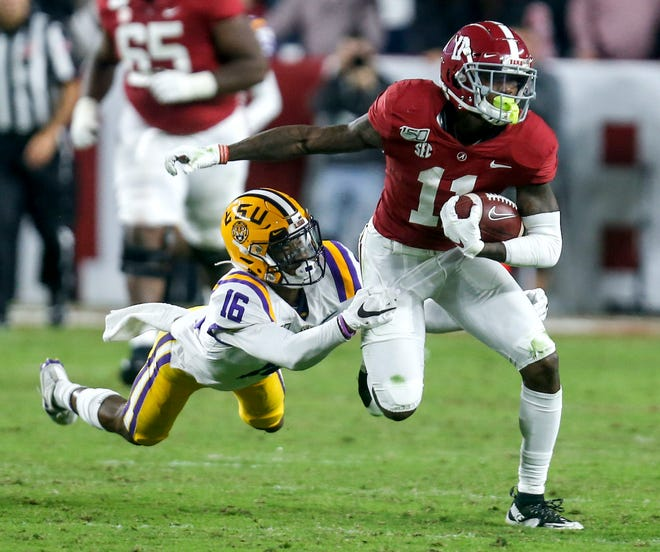 LSU cornerback Jay Ward (16) tries to bring down Alabama  receiver Henry Ruggs III after a reception during last year's game at Bryant-Denny Stadium.