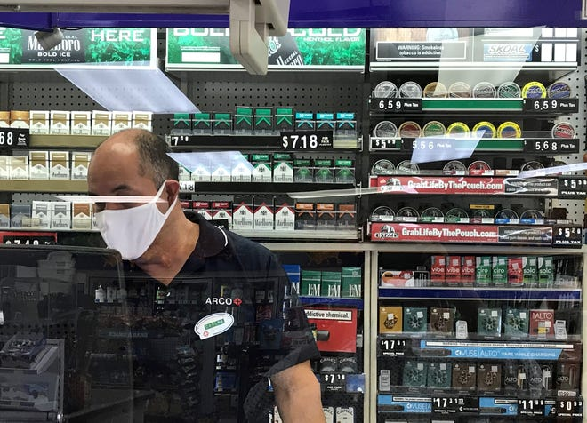 A cashier wearing a mask and gloves works behind a plastic partition at the Arco Food Mart on South Virginia Street in South Reno across from Whole Foods Market.