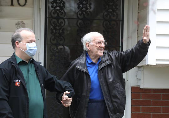 Friends and neighbors of Tommy Little of Gates  celebrate his turning 94-years-old today, Friday, April 24, 2020.  Stephen Farmer, holds onto to Tommy Little who waves to neighbors that came over to wish him happy birthday.  Farmer, whose family became friends with the Littles when they moved to Rochester from Scotland where Little is from, comes over once a week to help Little pay bills or take him to a doctor's appointment.  Little's wife died a couple of years ago.