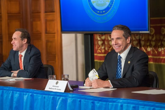 New York Gov. Andrew Cuomo holds an N95 mask sent to him by a retired Kansas farmer, whose letter Cuomo read at a briefing Friday, April 24, 2020.