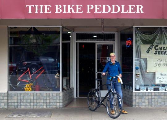 Robyn Saunders-Wilson displays a bike for sale at The Bike Peddler in Salem on April 24, 2020.